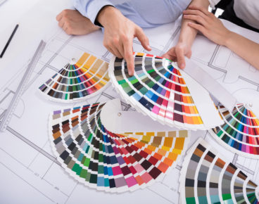 Close-up Of Two Architect's Hand Choosing Color From Various Colorful Swatches While Working On Blueprint