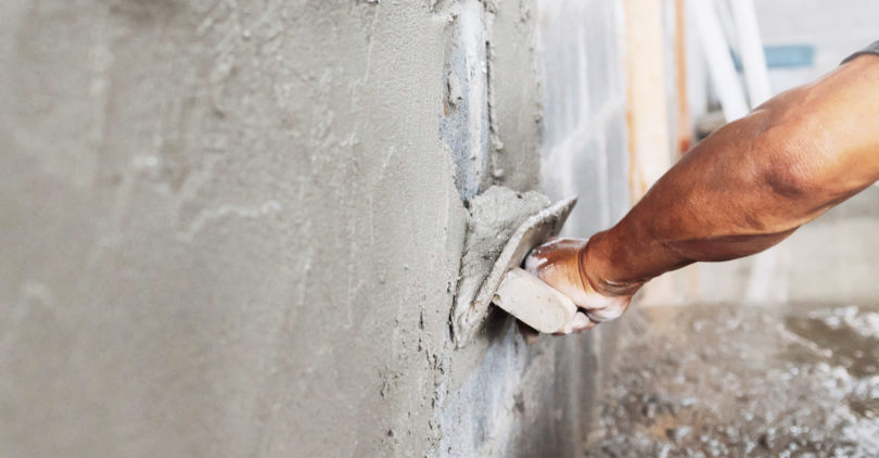 closeup hand of worker plastering cement at wall in construction site